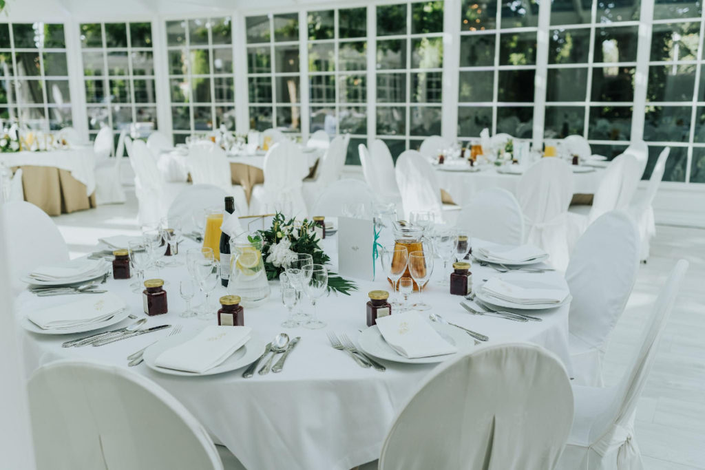 geometryczne złote bryły z kwiatami jako dekoracja okrągłych stolików gości