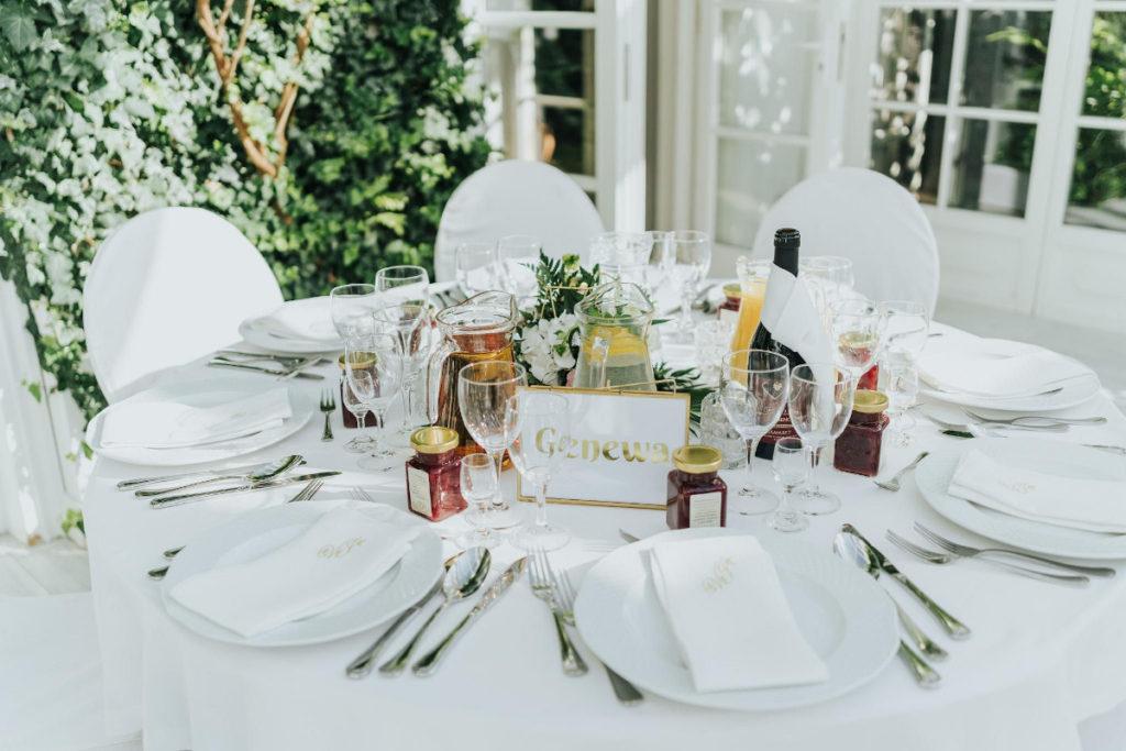złote elementy w postaci świecznika i ramki jako aranżacja stołu gości