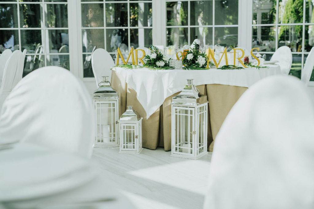 aranżacja stołu pary młodej z egzotycznych liści i złotych dodatków