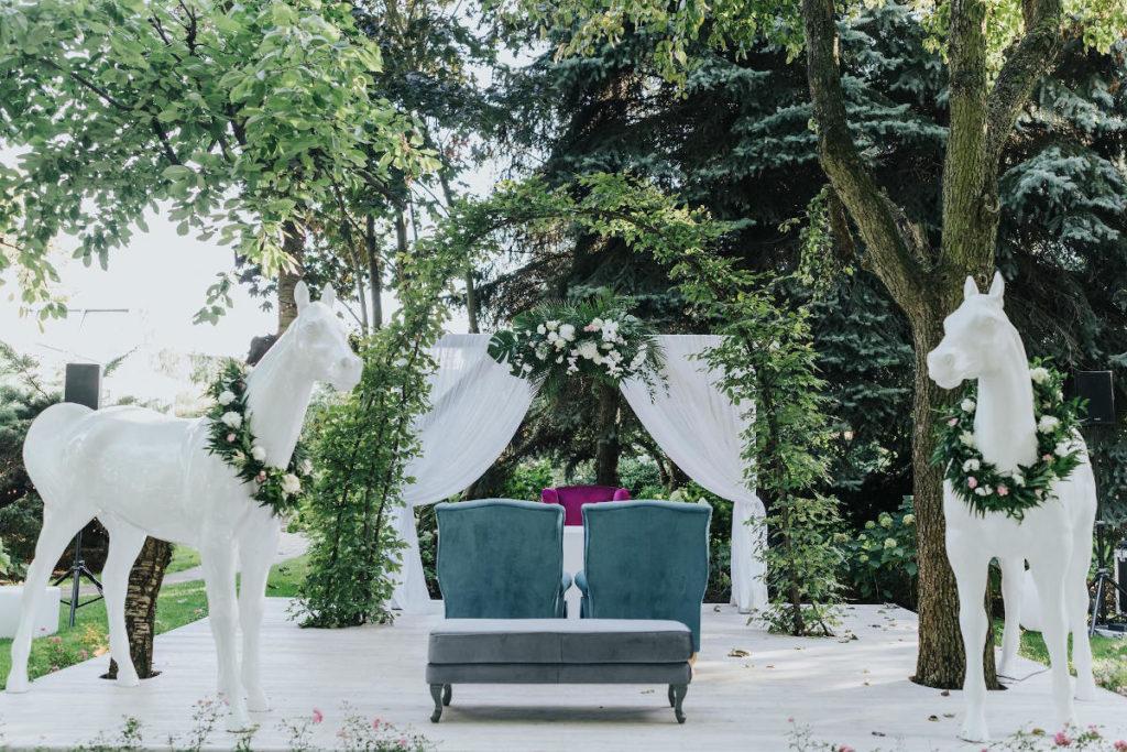 dekoracja miejsca ślubu plenerowego w postaci łuku materiału kolorowych mebli i białych koni