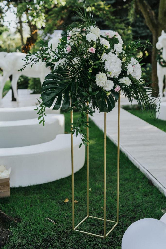 kompozycja z egzotycznych liści i białych kwiatów na złotym geometrycznym stojaku jako dekoracja pleneru do ślubu