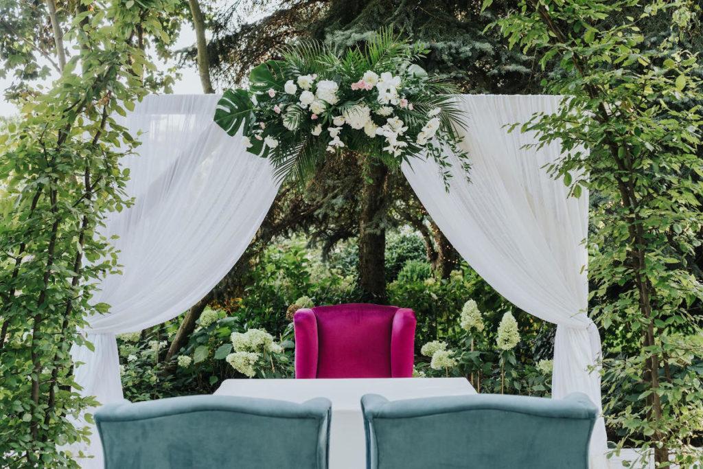dekoracyjne meble łuk materiał i kompozycja z egzotycznych kwiatów i liści jako dekoracja ślubu w plenerze