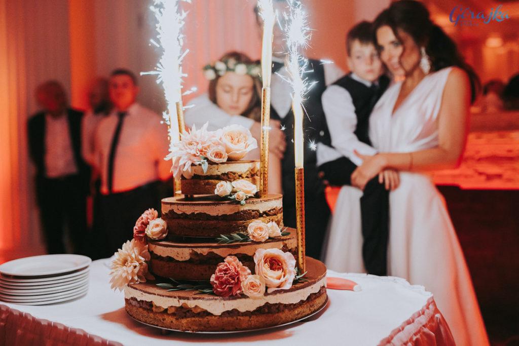 dekoracja pastelowymi kwiatami czekoladowego tortu ślubnego