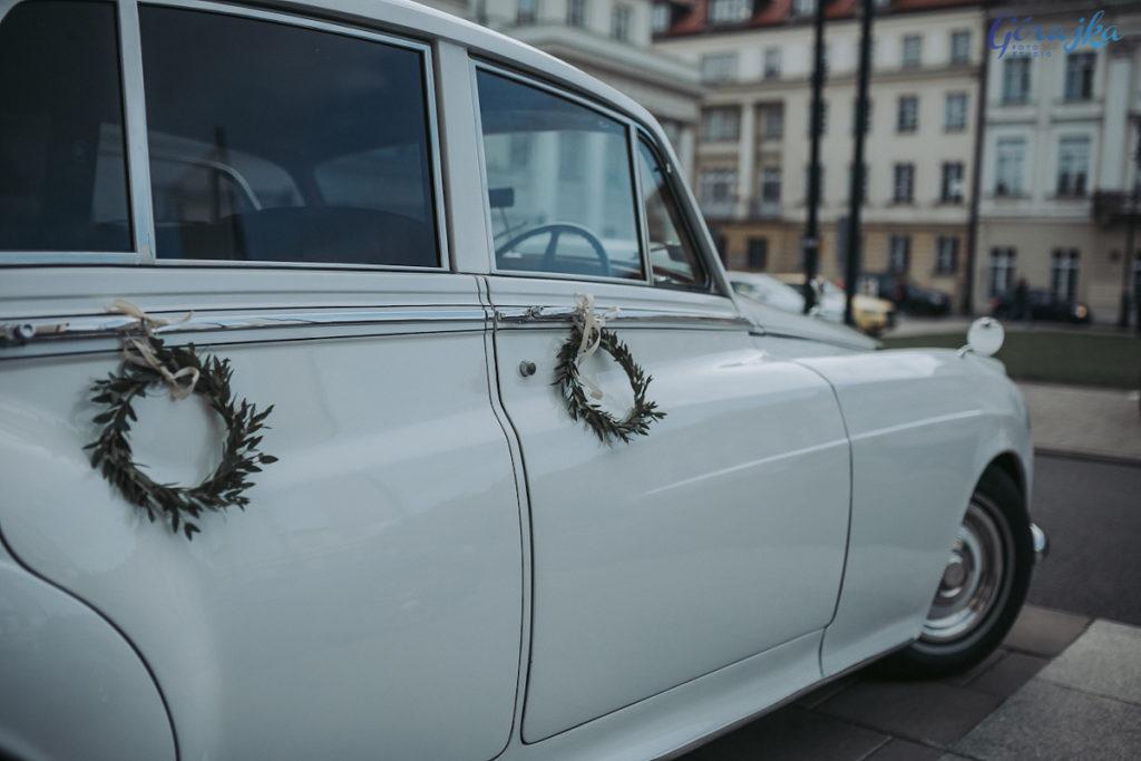 dekoracja zabytkowego auta do ślubu zielonymi wianuszkami do klamek