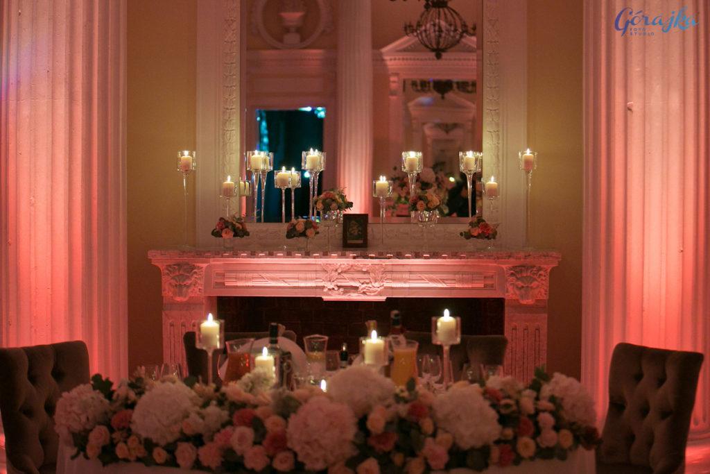 dekoracja kominka w tle za parą młodą świecami w szkle i kwiatami