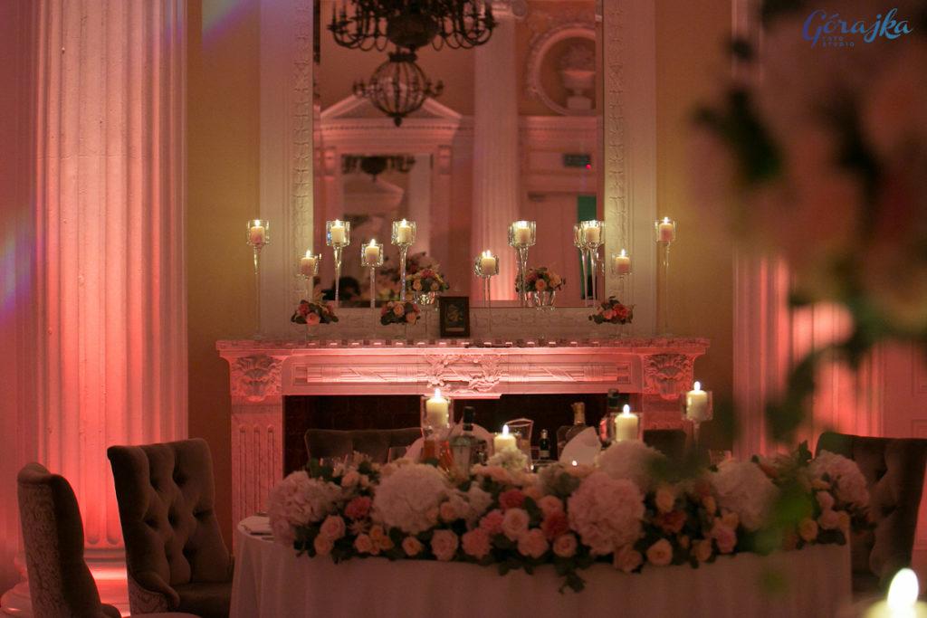 aranżacja z kwiatów i świec w szkle na kominku jako dekoracja tła za parą młodą oraz dekoracja stołu kwiatową girlandą