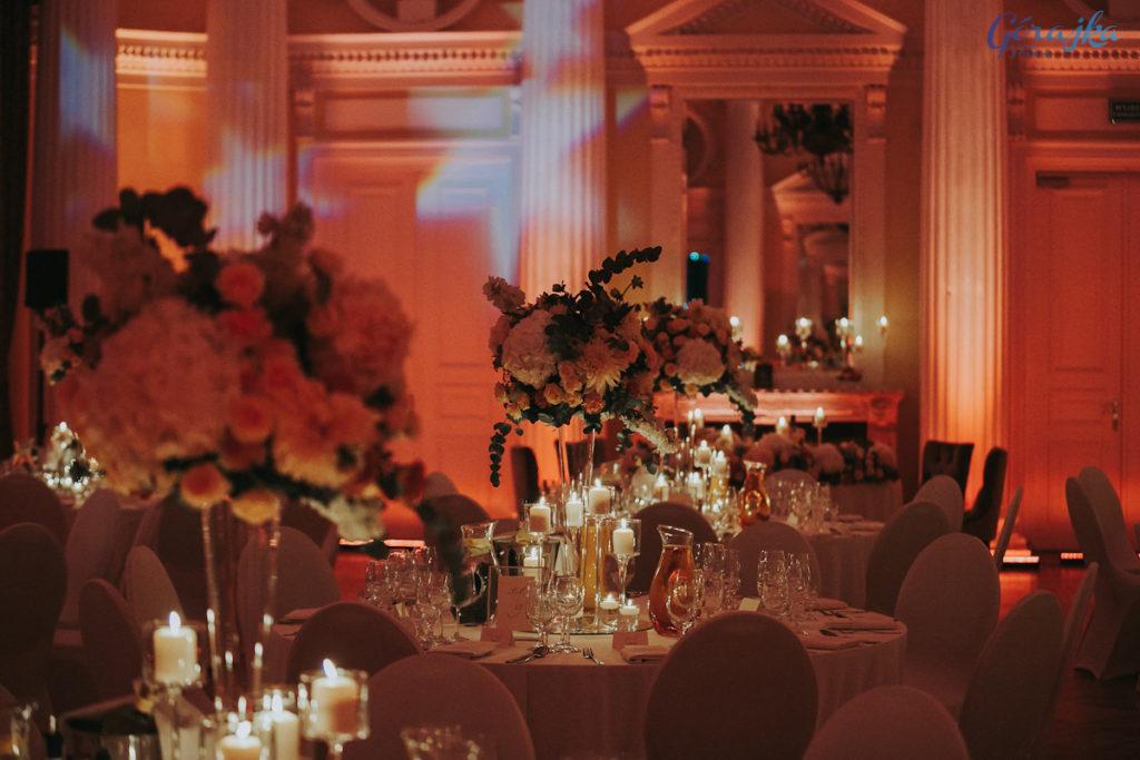 bukiety w wysokich wazonach na okrągłych stołach gości w otoczeniu świec
