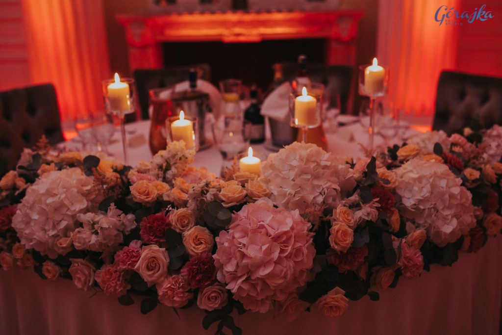 girlanda kwiatowa z hortensji i róż na stole pary młodej ze świecami w szkle