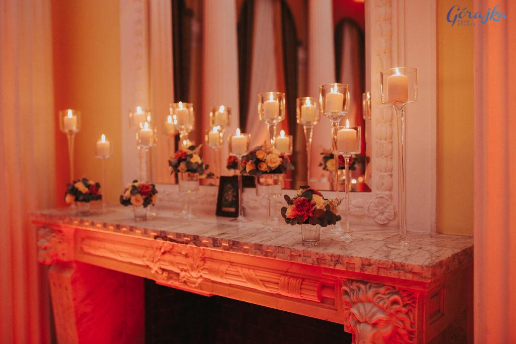 aranżacja ze świec w szklanych kielichach i małych kompozycji kwiatowych ustawionych na kominku