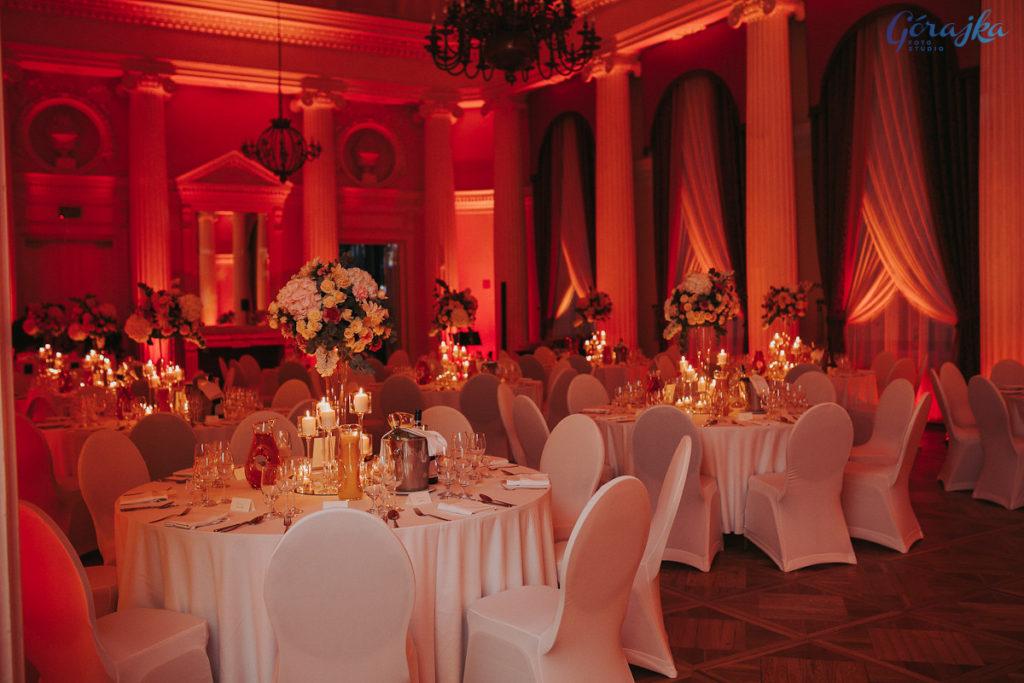 dekoracja okrągłych stołów weselnych wysokimi bukietami i świecami w szkle