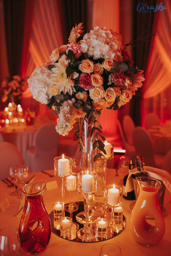 wysoka kompozycja kwiatowa na szklanych wazonie otoczona świecami w szkle i postawiona na lustrze
