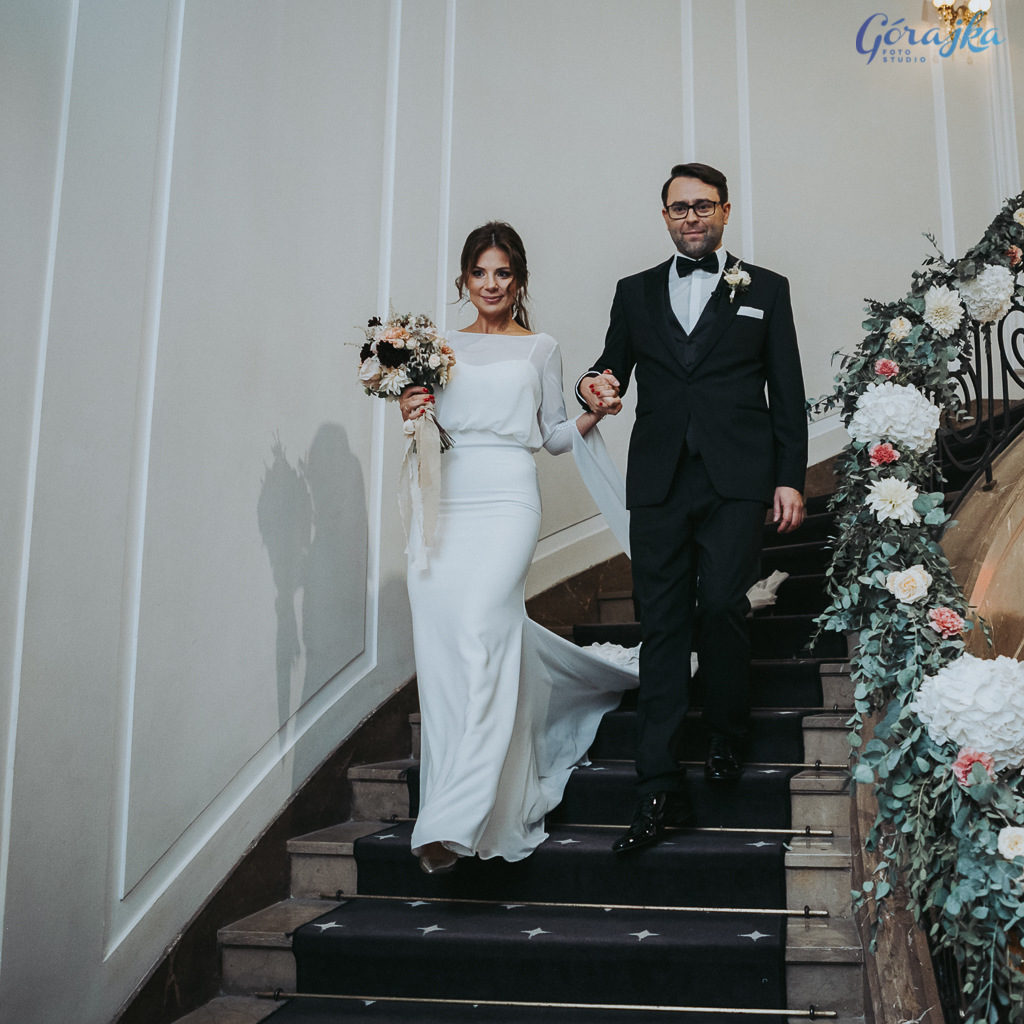 para młoda schodząca po schodach zdobionych zielenią i kwiatami