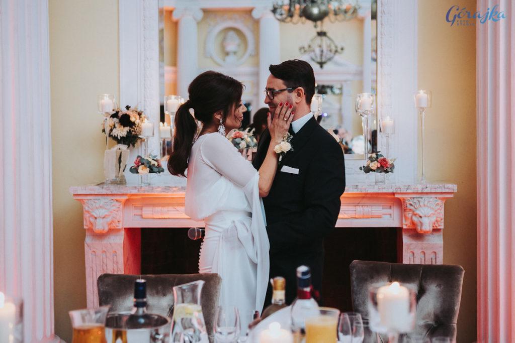 szczęśliwa para młoda na tle kominka w sali weselnej