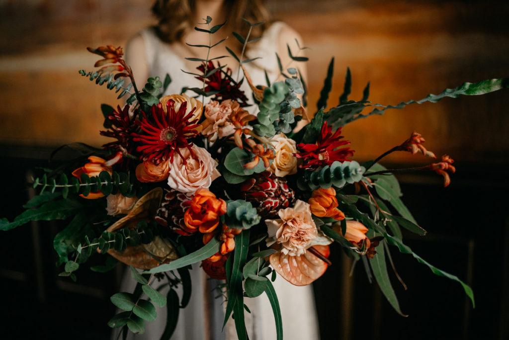 bukiet z pomarańczowych kwiatów tulipana i anturium oraz kremowych goździków i róż oraz bordowych gerber i protei