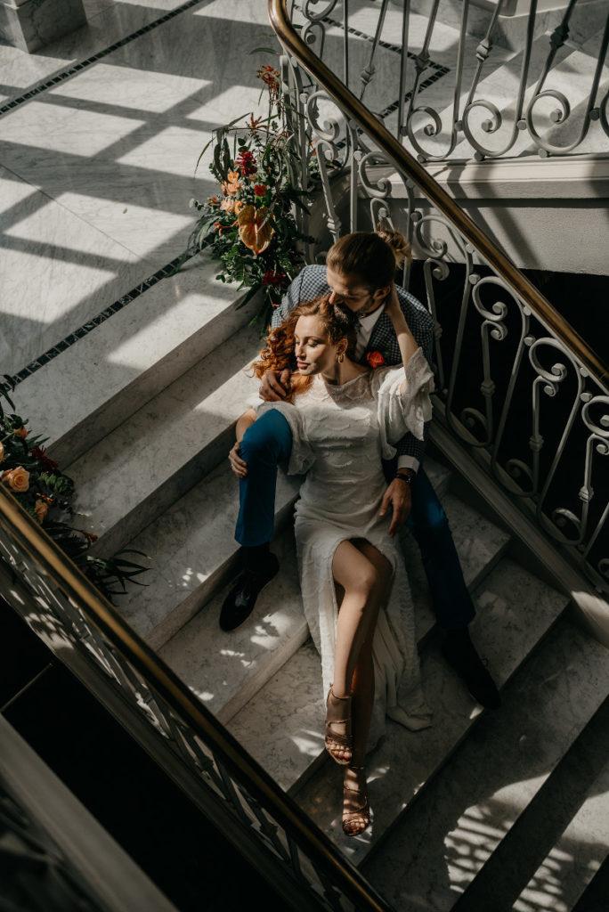 para modeli pozująca na schodach w otoczeniu kwiatów