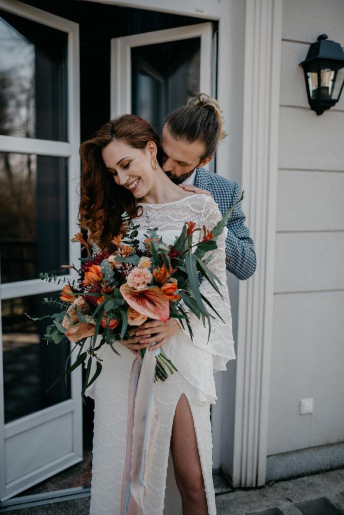 para modeli prezentuje odzież ślubną oraz wiązankę dla panny młodej
