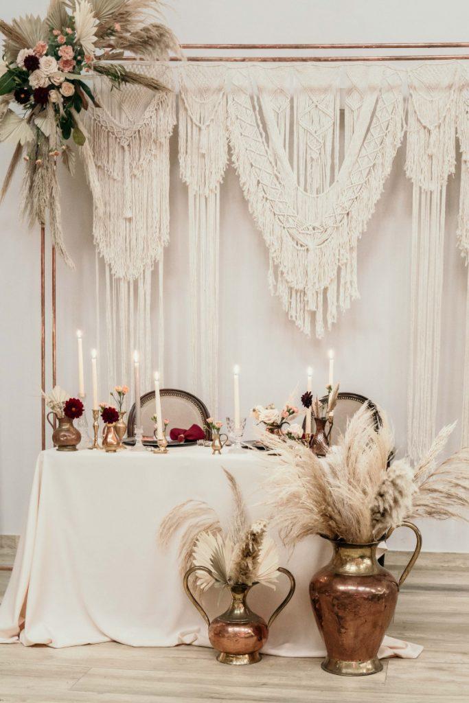 scenografia w stylu boho z wykorzystaniem makramy i miedzianych wazonów