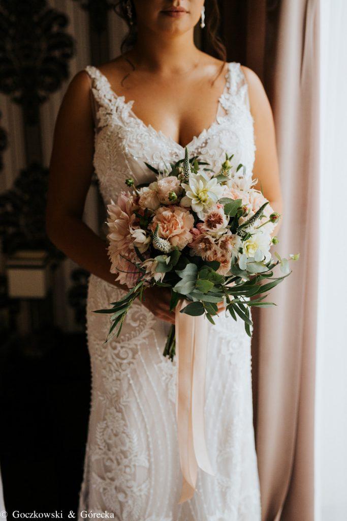 bukiet ślubny z brzoskwiniowych kwiatów i dodatków ze zwisającą wstążką