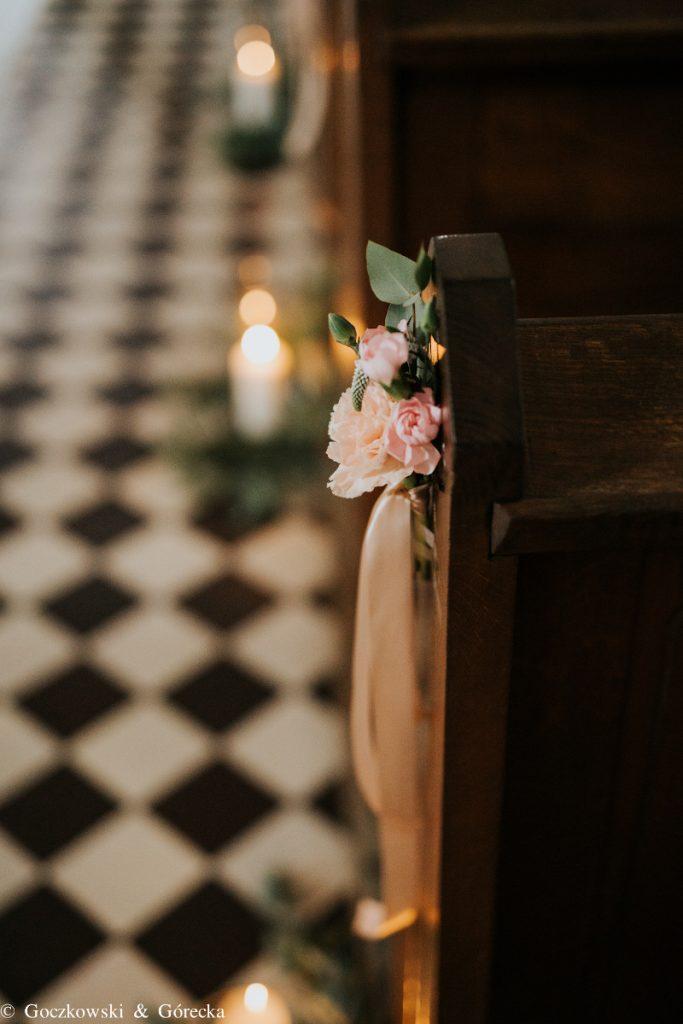 bukiecik pastelowych kwiatów ze wstążką przypięty do ławki na ślubie kościelnym