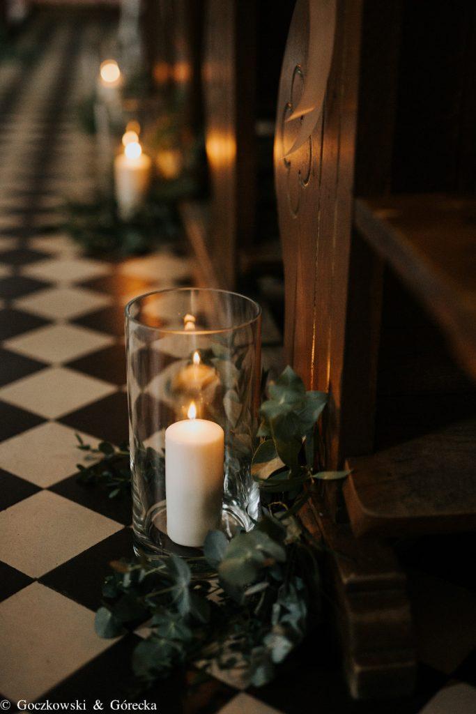 dekoracja świecami i zielenią nawy głównej kościoła do ślubu