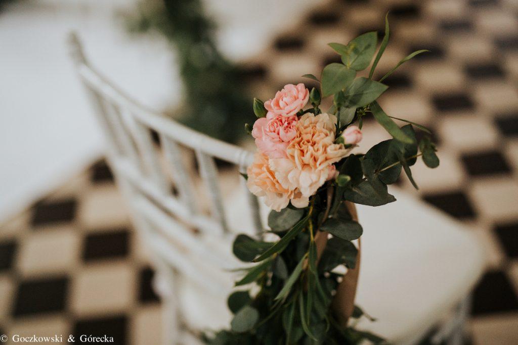 dekoracja bukiecikiem z pastelowych kwiatów i zieleni krzeseł do ślubu w kościele