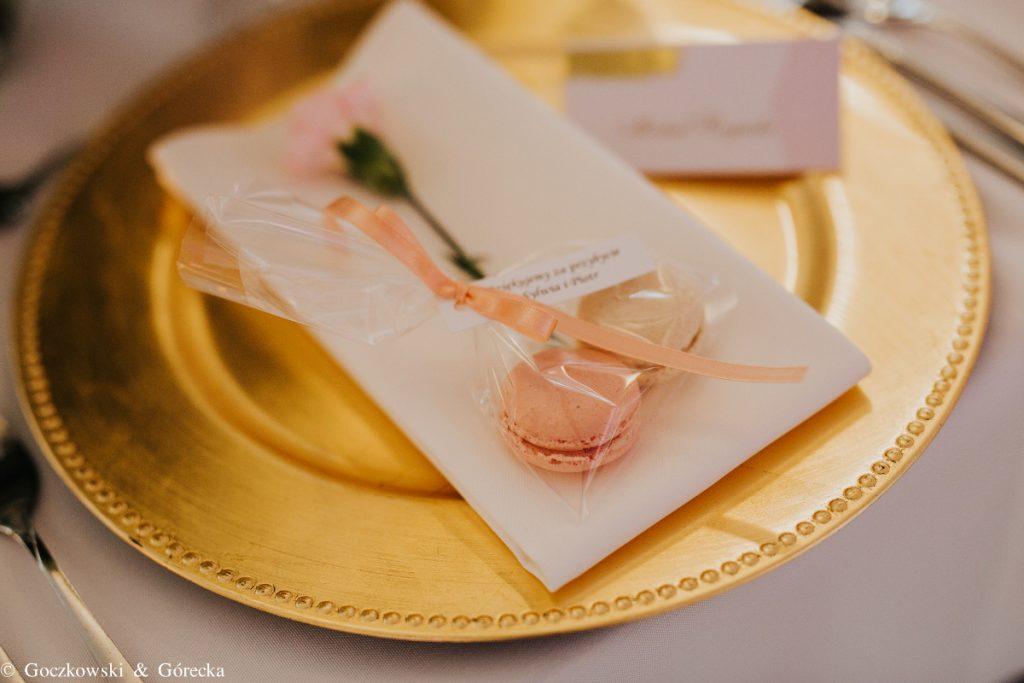 dekoracja stołu podtalerzami złotymi i prezencikami dla gości
