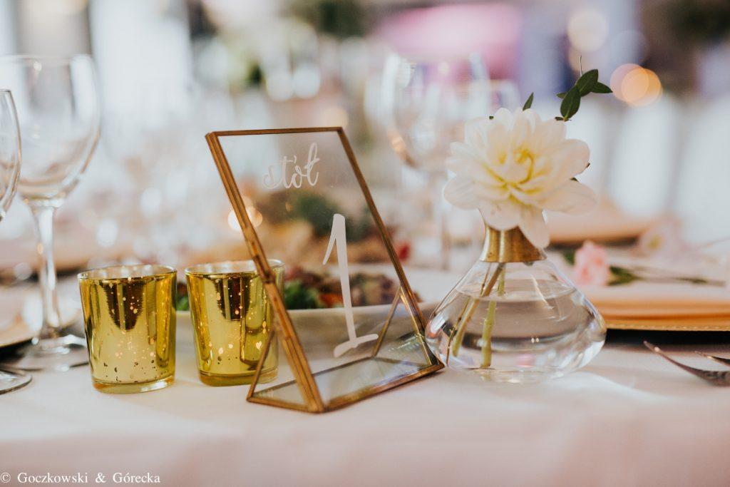 numeracja stołów w szklanej ramce z kwiatem w butelce