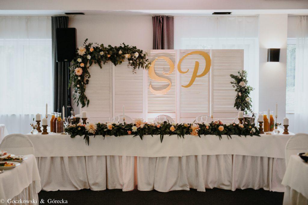 dekoracja stołu prezydialnego i tła za parą młodą zielenią i brzoskwiniowymi kwiatami