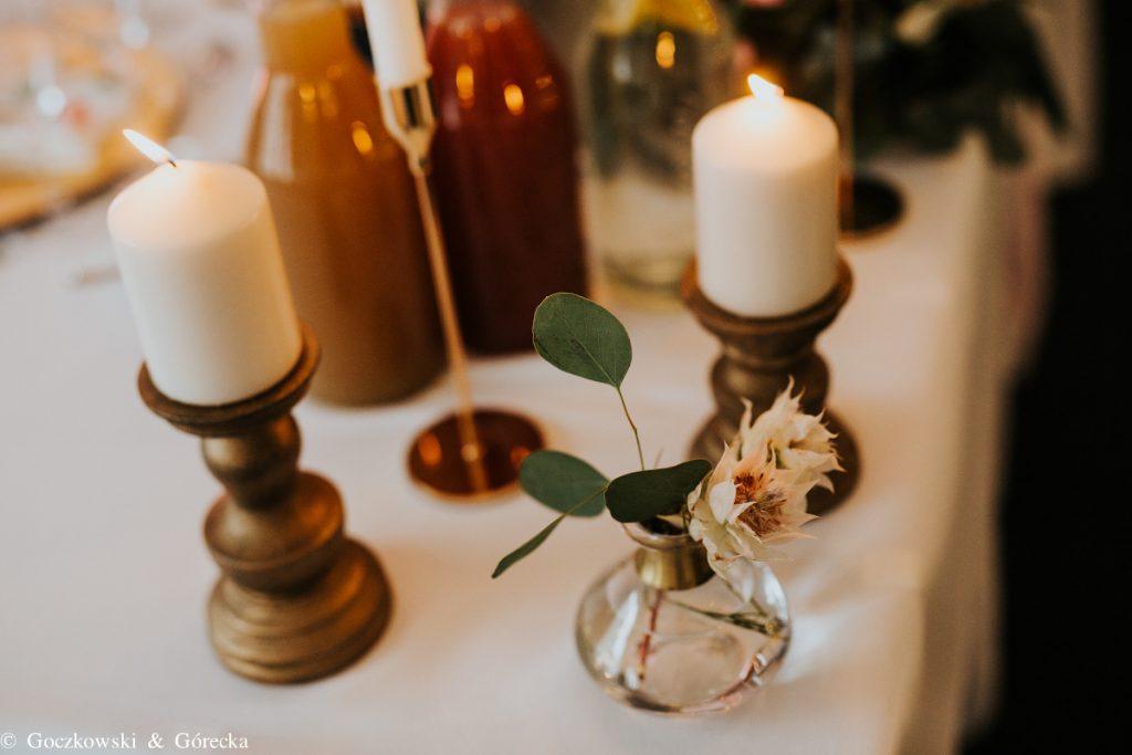 delikatne kwiatowe dodatki w towarzystwie złota na stole weselnym