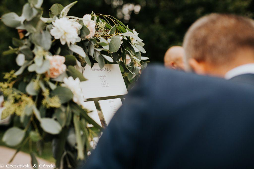 plan rozsadzenia gości ozdobiony girlandą z zieleni i pastelowych kwiatów