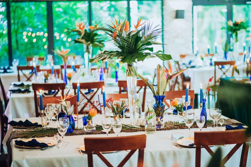 bukiet z egzotycznych liści i strelicji w szklanym wazonie oraz niebieskie butelki z nietypowymi kwiatami