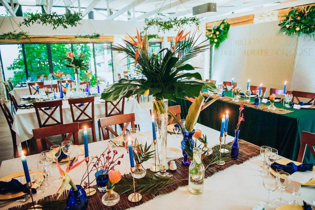 aranżacja ze strelicji i monstery oraz bieżniki z witek jako aranżacja stołów nakrycie stołu prezydialnego zielonym obrusem