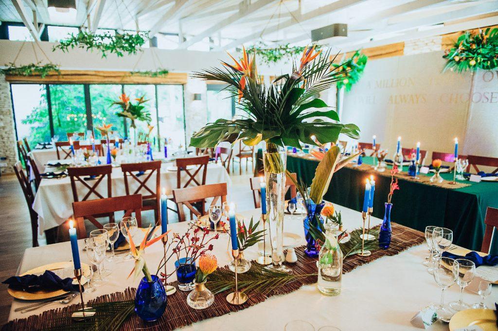 dekoracja sali weselnej w egzotycznym klimacie z użyciem liści palmowych i monsterą
