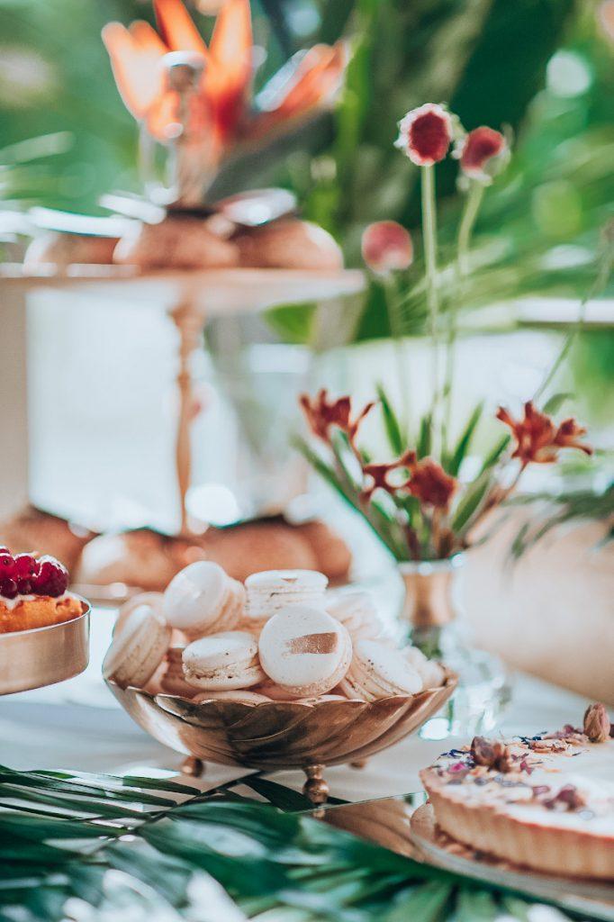 dekoracja stołu słodkiego na przyjęciu weselnym egzotycznymi roślinami i złotymi dekoracjami