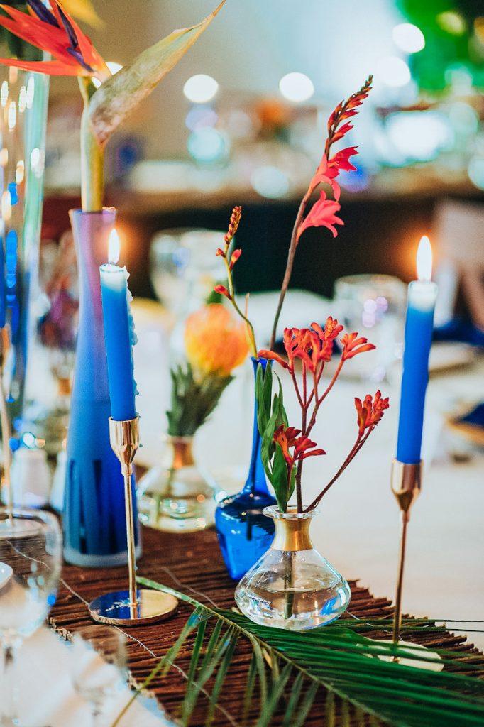 świece i butelki w kolorze ultramaryny oraz liście palmy jako dekoracja stołu weselnego