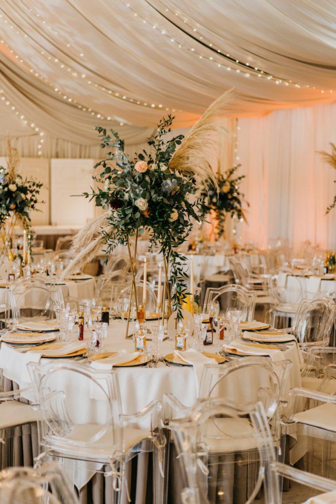 dekoracja kwiatowa z pampasami na wysokim złotym stojaku jako dekoracja stołu w stylu boho glam