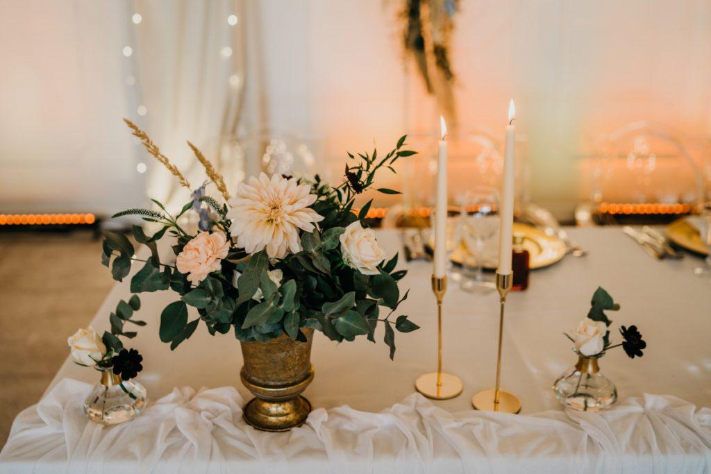 kompozycja z zieleni i kwiatów w złotej wazie i świece w złotych świecznikach jako dekoracja stołu prezydialnego
