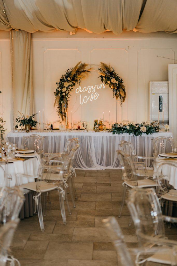 dekoracja stołu prezydialnego i tła brzoskwiniowymi kwiatami i pampasami