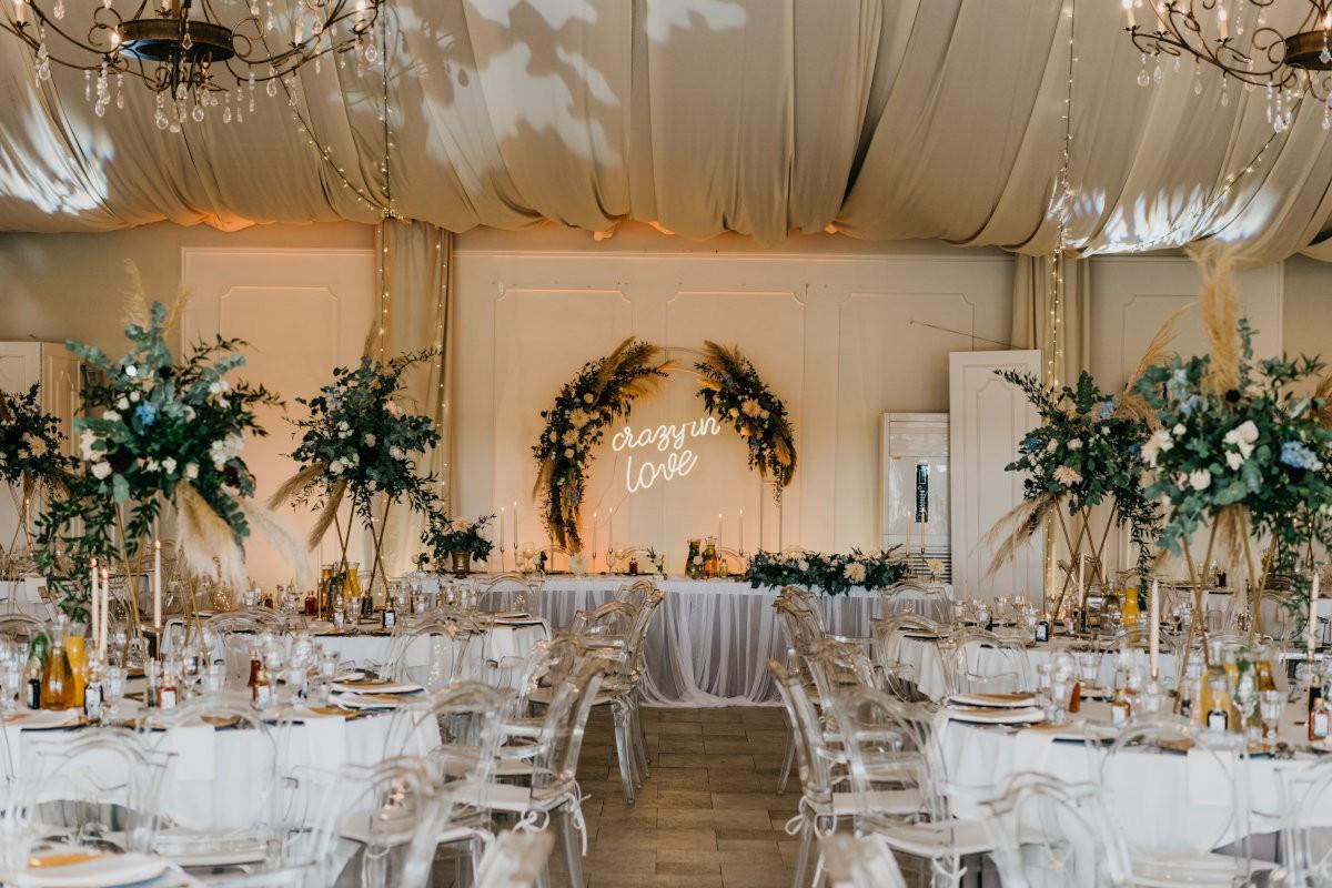 aranżacja sali na przyjęcie weselne kompozycjami kwiatowymi z trawami pampasowymi