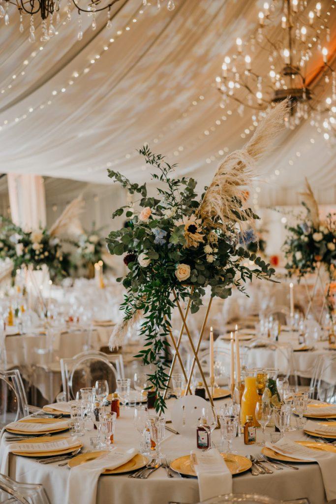 kompozycja z brzoskwiniowymi i błękitnymi kwiatami na stół gości