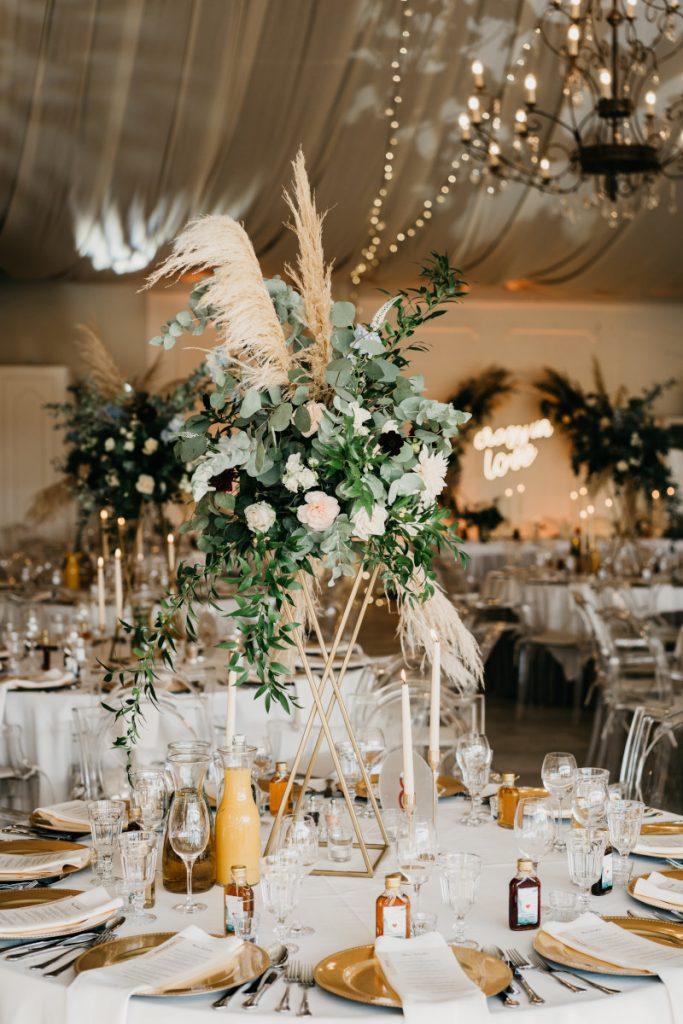 dekoracja stołu gości wysoką kompozycją na złotym geometrycznym stojaku