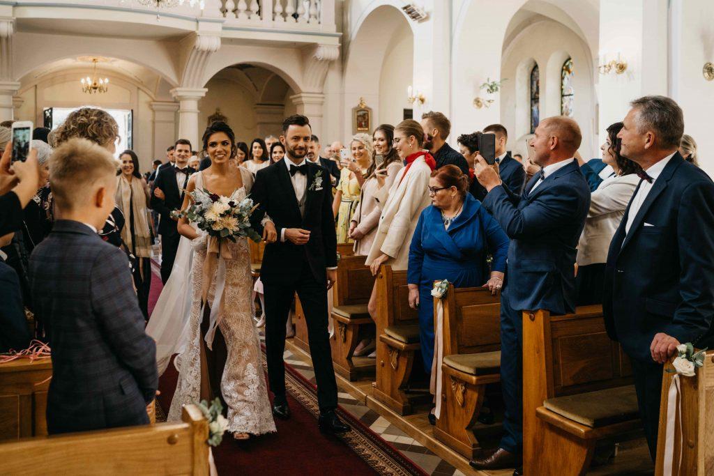 dekoracja ławek bukiecikami z kwiatów i długimi wstążkami do ślubu