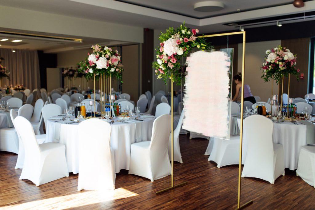 kwiaty w kolorach białych i różowych jako dekoracji sali weselnej