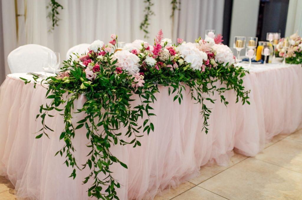 kompozycja kwiatowa z dodatkiem zielonych liści dekorująca stół pary młodej w ogrodowym stylu