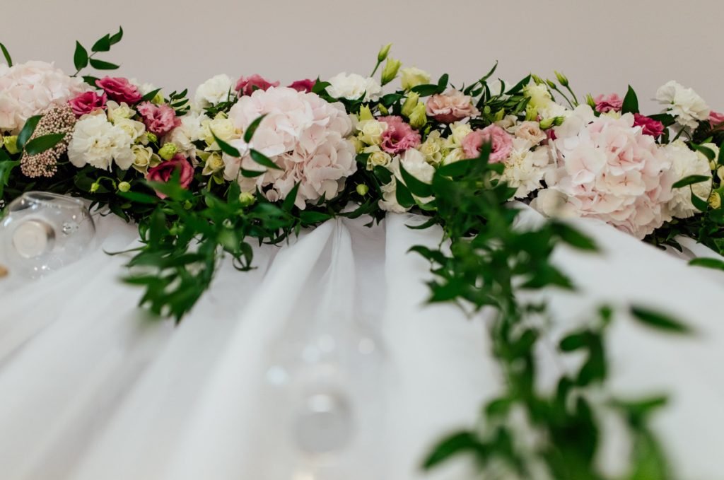 girlanda z różowych kwiatów i zieleni dekorująca ściankę za parą młodą