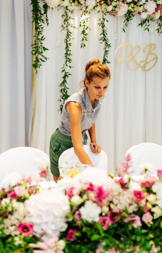 dekoratorska przy pracy na sali weselnej układająca dekorację na stole