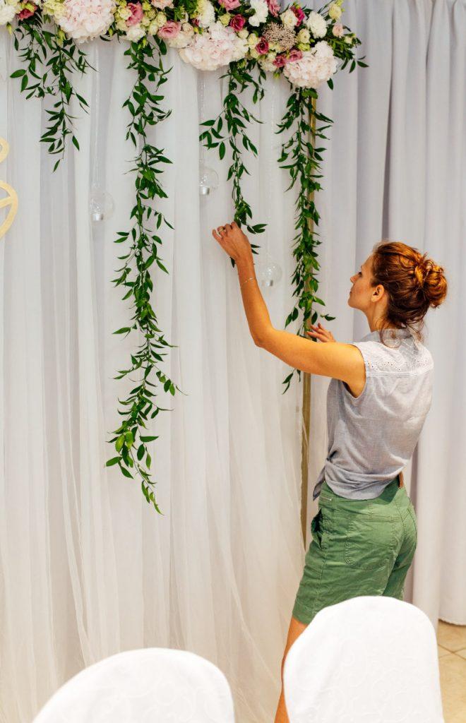 florystka poprawiająca zieleń dekorująca tła za parą młodą
