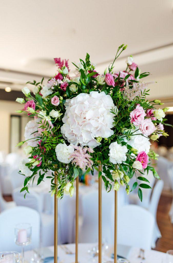 kompozycja z różowopudrową hortensją i ciemnoróżowymi kwiatami z zielonymi listkami