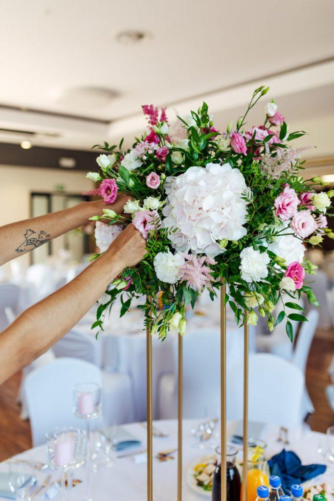 florystka uzupełniająca kompozycję kwiatową na stole gości