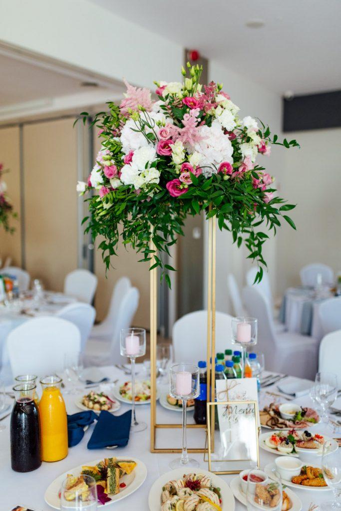 dekoracja stołu gości kompozycją z kwiatów i zieleni oraz świecami różowym w szkle